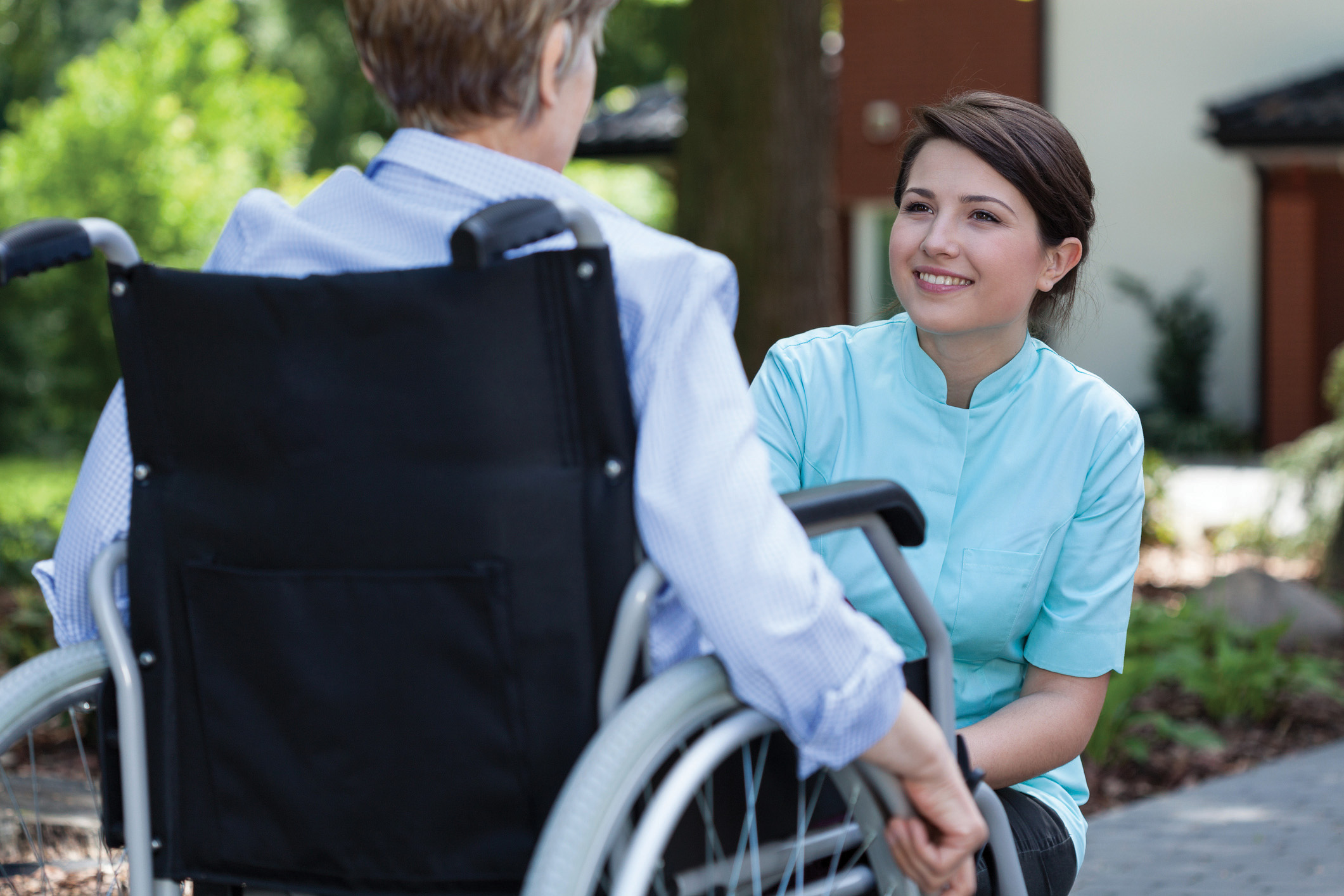 Nurse in lab coat smiles to the woman in the wheelchair